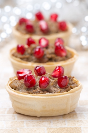 christmas catering: festive appetizer - tartlets with liver paste and pomegranate seeds, close-up, vertical