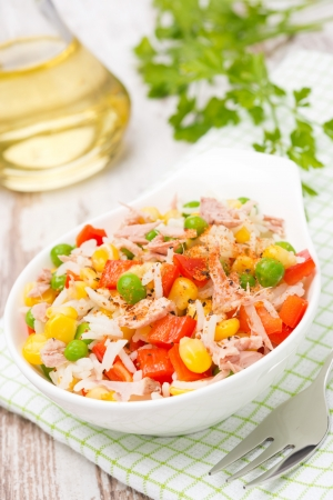 salad with corn, green peas, rice, red pepper and tuna in a bowl, close-up photo