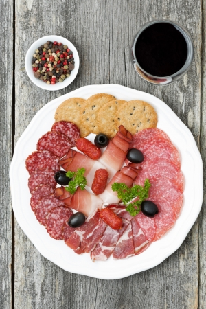 assorted deli meats and a glass of wine, top view, vertical
