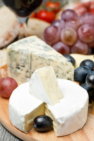 antipasto platter: Camembert, blue cheese, grapes and walnuts on wooden board, vertical