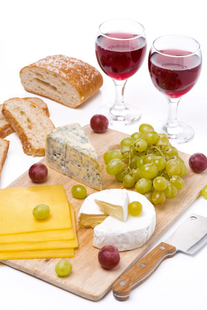Cheese platter, grapes, bread and red wine on a wooden board, vertical photo
