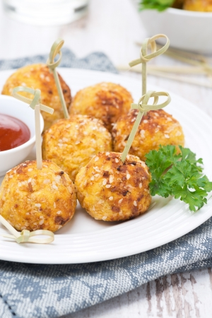 breading: chicken meatballs in breading with tomato sauce, closeup, vertical