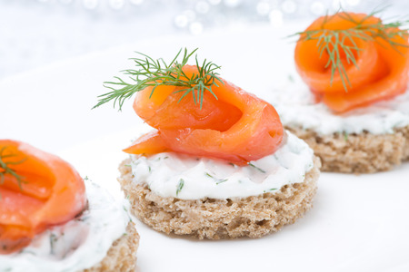 festive appetizer - canape with rye bread, cream cheese, salmon and herbs, close-up Stock Photo
