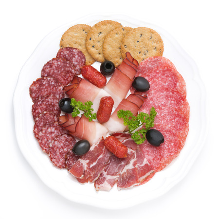 plate of meat delicacies and crackers, isolated on white