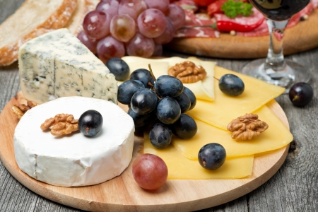 cheese platter: Assorted cheese, grapes, wine and sausages on wooden board