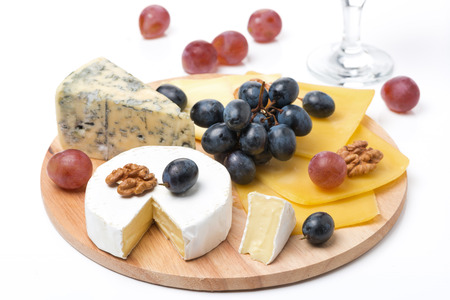 assorted cheeses, grapes and glass of wine on wooden board, isolated on white photo