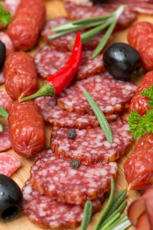 Assorted meats and sausages on a wooden board, close-up, vertical photo