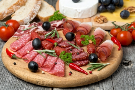 Assorted meats and sausages on a wooden board, horizontal photo