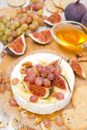 Camembert with grapes, figs, honey, crackers and walnuts, top view, vertical photo
