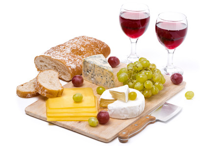Cheese platter, grapes, ciabatta and two glass of red wine isolated on white photo