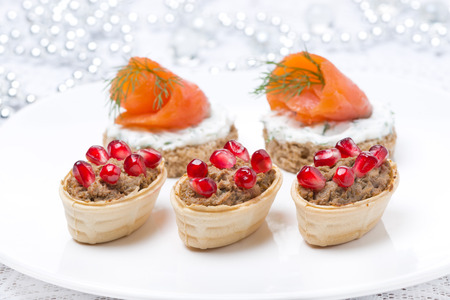holiday appetizers - canape with salmon and tartlet with liver pate, close-up Foto de archivo
