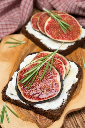 rye bread with goat cheese, fresh figs, honey and rosemary, close-up, vertical photo
