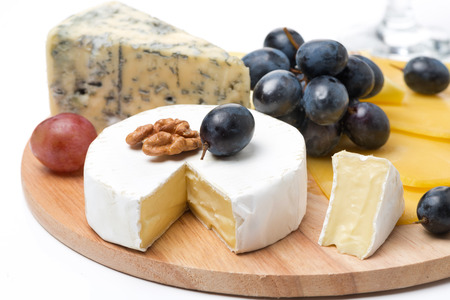 Assorted cheeses and grapes on a wooden board, isolated on white