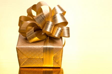 Christmas gift box on a golden background, close-up, horizontal photo