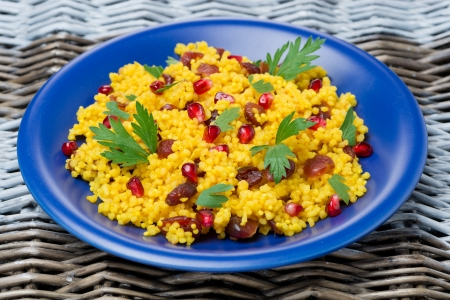 couscous salad with curry, cranberries and herbs on the blue plate, close-up photo