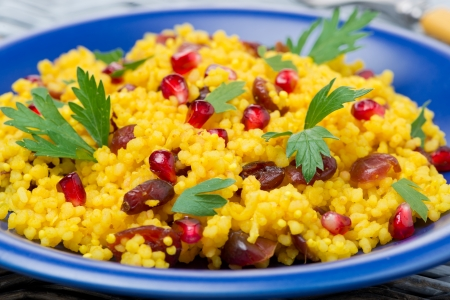 couscous salad with curry, dried cranberries and herbs, close-up, horizontal photo