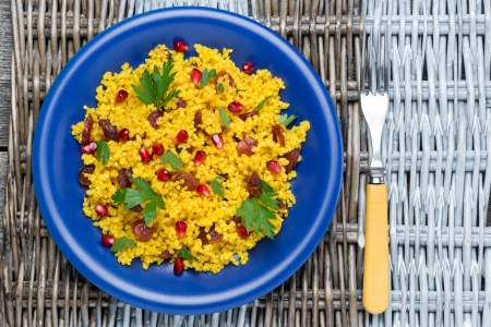couscous salad with curry, dried cranberries and herbs, top view, close-up photo
