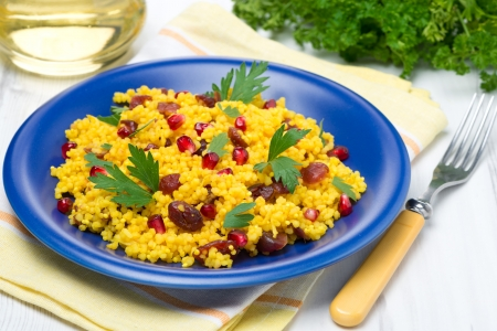 couscous with curry, dried cranberries and herbs on the blue plate, close-up photo