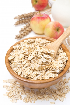Oat flakes in a bowl and apples in the background, isolated on white