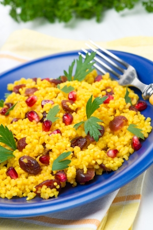 couscous with curry, dried cranberries and herbs on the plate, vertical photo
