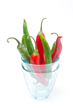 Red and green chili peppers in a glass, isolated on white photo