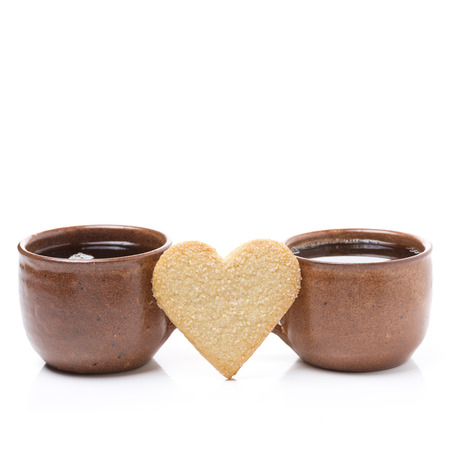 two cups of coffee and cookies in the shape of hearts for Valentine's Day, isolated on white photo