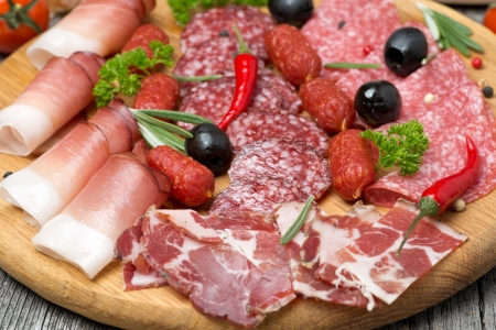 meats: Assorted meats and sausages, olives and spices, close-up, horizontal Stock Photo
