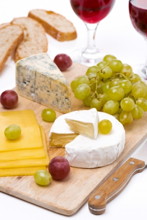 Cheese platter, grapes, ciabatta and two glass of red wine, close-up, vertical photo