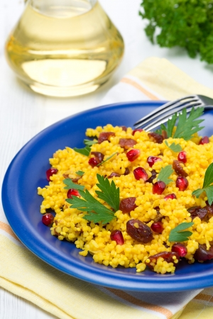 couscous with curry, dried cranberries and herbs, vertical, close-up photo