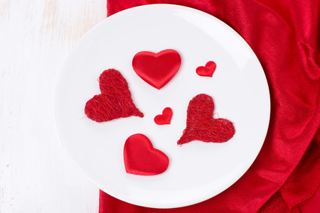 plate with different red hearts, concept, top view, horizontal photo