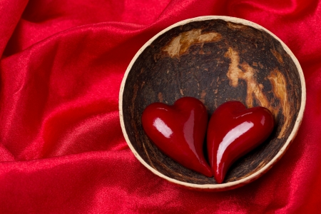 two hearts in a bowl of coconut on red satin background, close-up photo