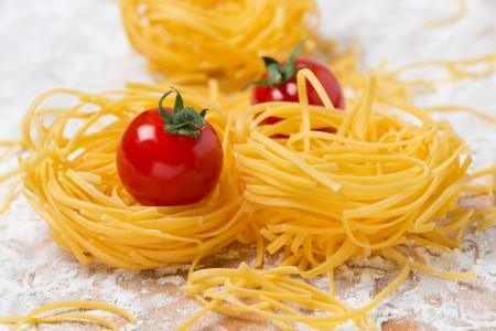 Italian egg pasta nest, cherry tomatoes on a cutting board sprinkled with flour, close-up photo