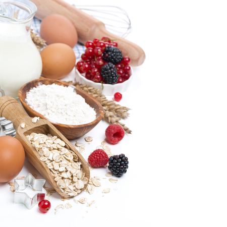 bakery products: oatmeal, flour, eggs and berries - the ingredients for baking, isolated on white