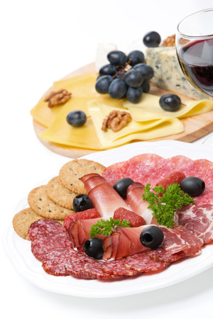 assorted deli meats, plate of cheese and a glass of wine, isolated on white photo
