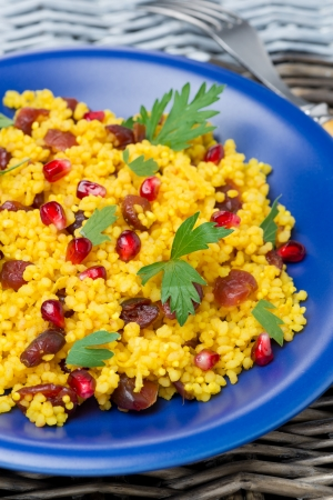 couscous salad with curry, dried cranberries and herbs, vertical, close-up photo