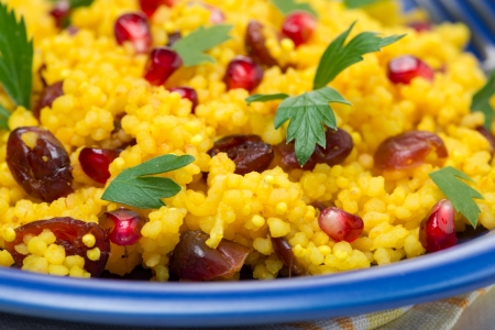 couscous with curry, dried cranberries and herbs, close-up photo
