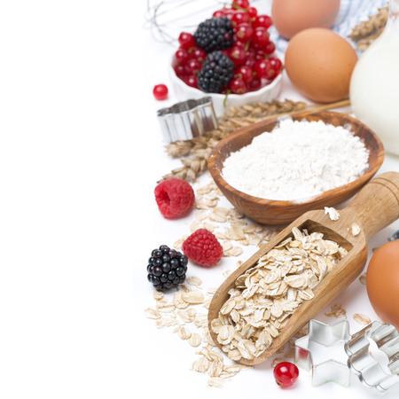 Haferflocken, Mehl, Milch, Eier und Beeren - die Zutaten für die Plätzchen backen, isoliert auf weiß Standard-Bild