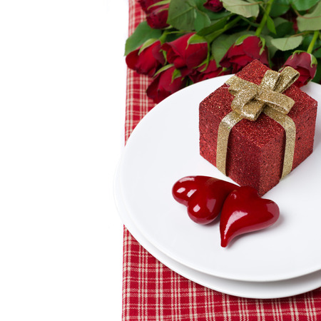 red gift box and two hearts on a plate, roses in the background, isolated on white photo