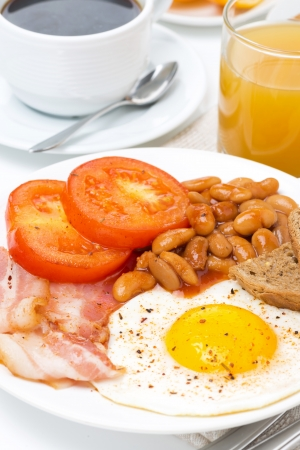 Traditional English breakfast with fried eggs, bacon, beans, coffee and juice, close-up photo