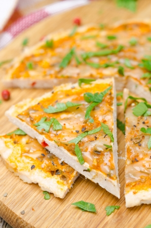 sliced ​​chicken pizza with tomato sauce, cheese and parsley on a wooden board, close-up photo