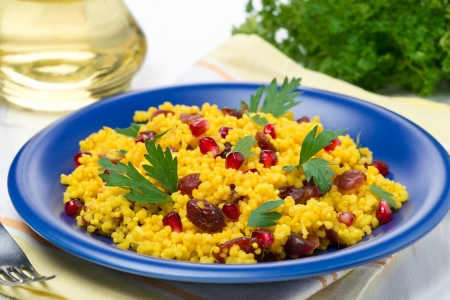 couscous with curry, dried cranberries and herbs, horizontal photo
