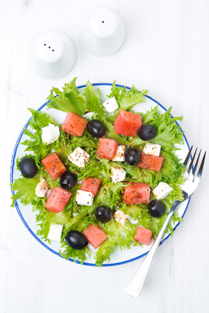 fresh salad with watermelon, feta cheese and olives, vertical, top view photo