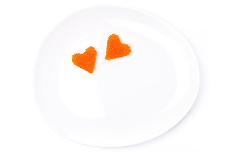 two hearts of red caviar on a plate, isolated on white photo