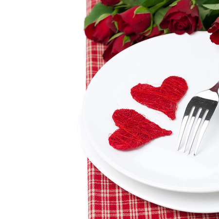 two wicker heart on a plate and red roses, isolated on white photo