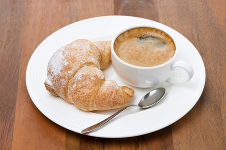 fresh croissants on a plate and cup of coffee on wooden background photo