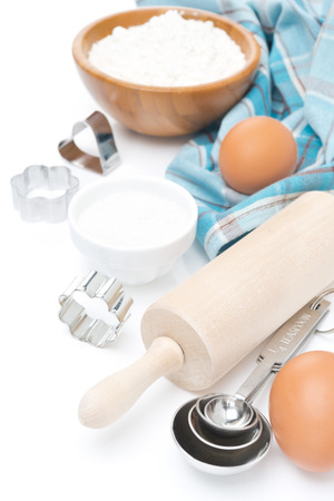 rolling pin, measuring spoons, cookie cutters and baking ingredients, isolated on white photo