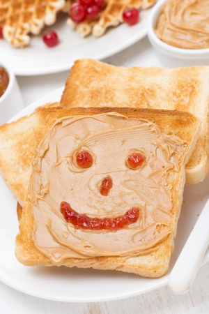 toast with peanut butter and drawing of jam, close-up, vertical photo
