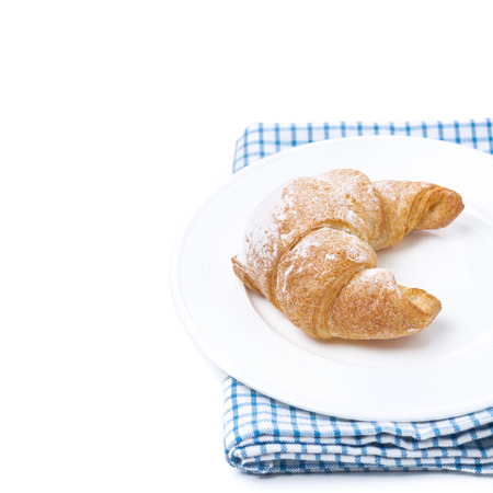 fresh croissant on a plate, isolated on white photo