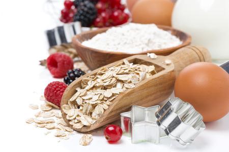 Haferflocken, Mehl, Milch, Eiern und frischen Beeren - die Zutaten für die Plätzchen backen, close-up Standard-Bild