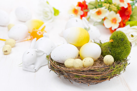 basket with easter eggs, flowers and rabbits, close-up photo
